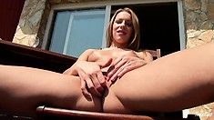 Blonde gives a show on the balcony and then rubs her cum catcher