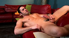 The horny guy strokes his cock until his belly gets covered with cum