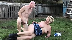 Chubby old bitch rides a younger man's big dick out on a field