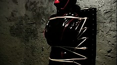 Latex bound slave gets tied up to a wall by her freaky mistress