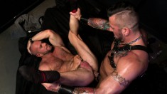 Two muscled hunks in black leather fulfill their oral and anal fantasies